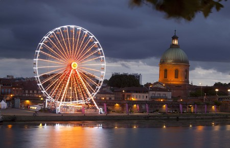 Big wheel at night with lights and the dome, Toulouse, France