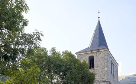 saint: Saint Jacques church in Saint Lary near a tree, France Stock Photo