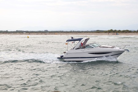 pleasure craft: white boat arriving at the spanish coast making waves Stock Photo