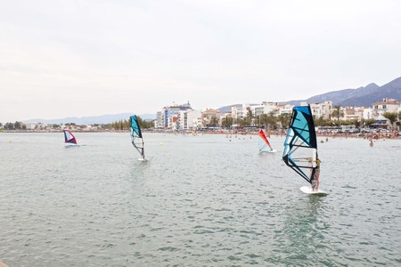 windsurfers: several windsurfers learning near the coast in the summer