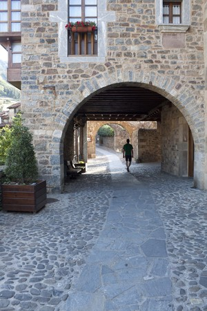 guy walking through the street in a stoned village, Potes, Spain Stock Photo