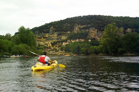 man canoeing with a yellow oar by the river in France