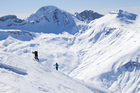 two skiers going up a mountain in a touring ski day Foto de archivo