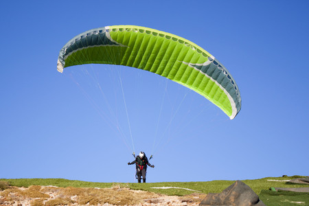 man running to star flying in a mountain with his paragliding