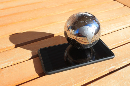 world globe over a mobile on a wood table in a sunny day
