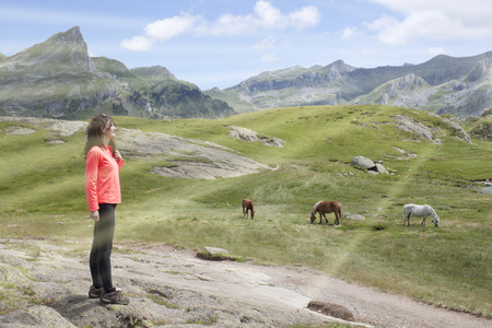 woman very happy in the mountain with horses