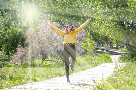 happy woman hopping in the park celebrating her success 版權商用圖片