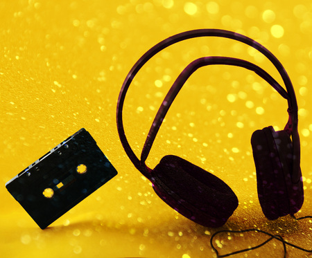 headphones and a cassette in a yellow background with lights Stock Photo