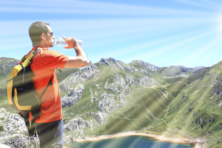 man drinking water in front of a Saliencias lake in Asturias, Spain 스톡 콘텐츠