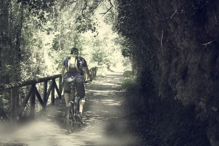 cyclist in the bear path with dust  in Asturias, Spain