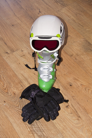 boot, helmet, gloves and blizzard sunglasses over a wooden floor