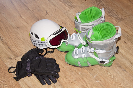 boots, helmet, gloves and blizzard sunglasses over a wooden floor Фото со стока