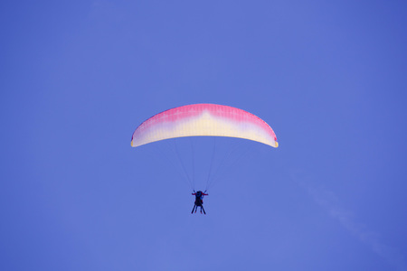 parachute flying up in the sky with skies in a cloudless day 스톡 콘텐츠