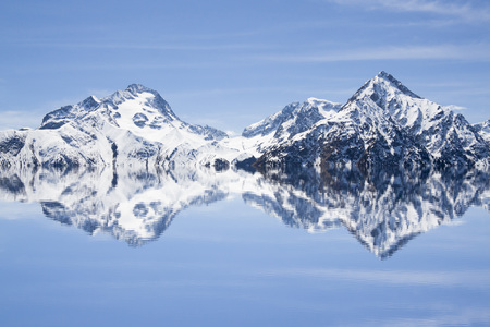 Reflection of mountains covered of snow in the water 스톡 콘텐츠