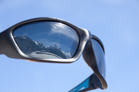 sunglasses reflecting mountains covered of snow in winter, alps