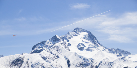 parachute and a plane flying in the sky over a snowed mountain 스톡 콘텐츠