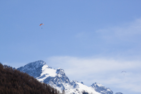 two parachutes flying over mountains in the sky