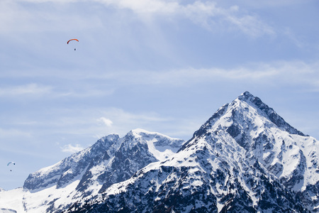 two parachutes flying in the sky over a snowed mountain