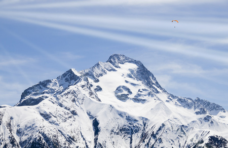 two parachutes flying with rays of sun in the sky over a snowed mountain 스톡 콘텐츠