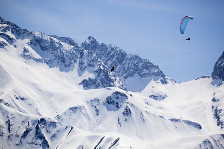 one blue parachute flying in the sky over a snowed mountain