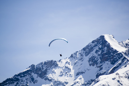 one blue parachute flying in the sky over a peak