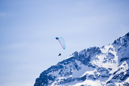 one blue parachute over flying a snowed mountain Imagens