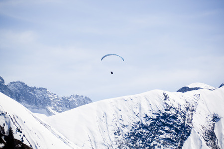 one blue parachute flying free in the sky over a snowed mountain