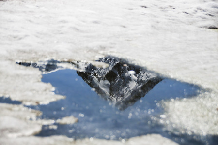 snowed peak refected in a puddle made by melting