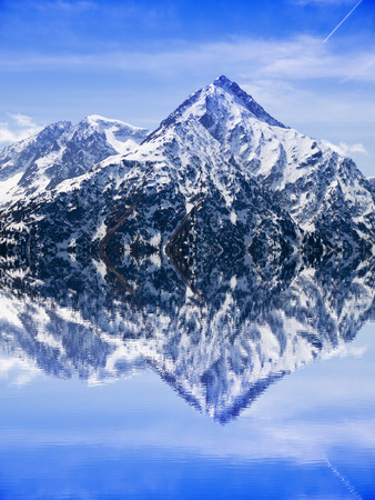 Reflection of a peak covered of snow in the water