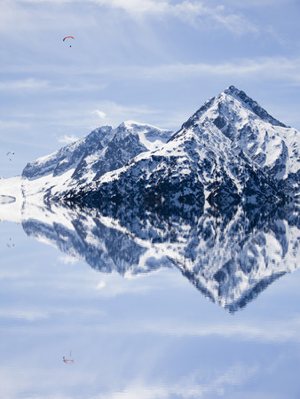 Reflection of two mountains covered of snow in the water
