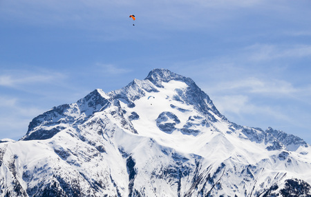 two parachutes flying in paralell in the sky over a snowed peak 스톡 콘텐츠