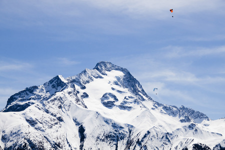 two parachutes flying in paralell over a snowed mountain