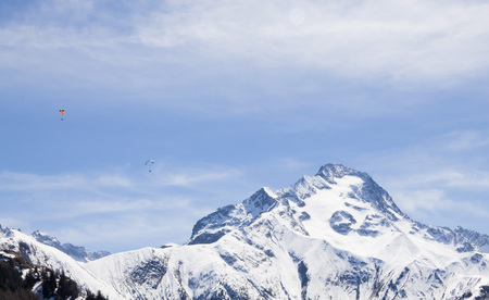 two parachutes flying in paralell in the sky over a snowed mountain
