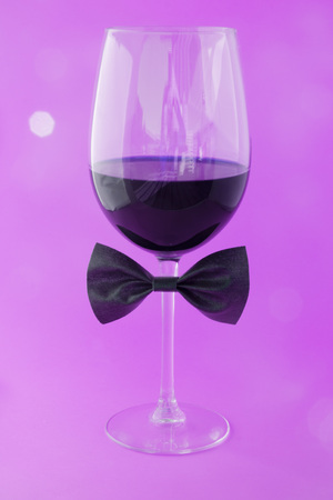 cup of wine in a pink background with a bow tie