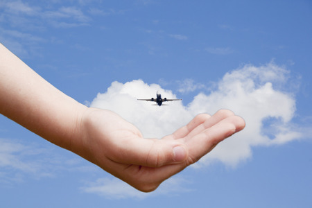 hand taking a plane flying in the sky 스톡 콘텐츠