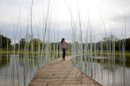 woman in a wooden path over a lake