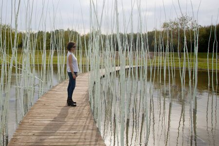 woman in a wooden path over a lake contemplating 스톡 콘텐츠