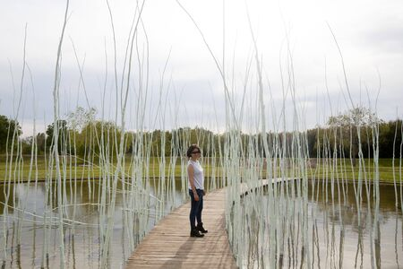 woman in a wooden path over a lake smiling 스톡 콘텐츠