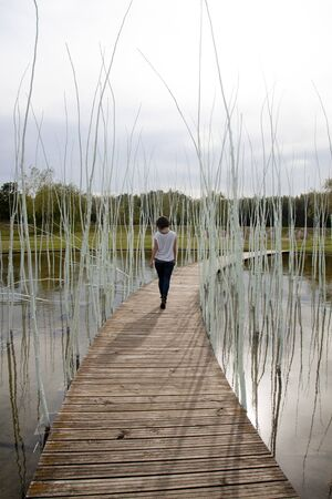 woman in a wooden path over a lake walking