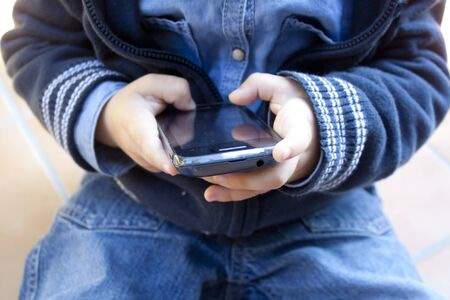 child playing in the mobile phone with his little hands