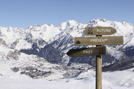 three signs indicating the way to the past, present and future over the mountains covered of snow Stock fotó