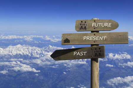 three signs indicating the way to the past, present and future over the mountains