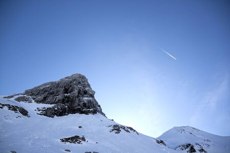 peak of a range mountain with the sun behind in a morning day