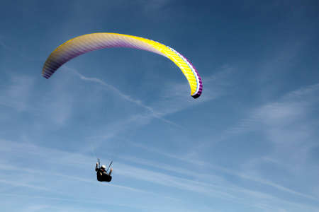 Man flying in the sky with a paraglide in a blue day