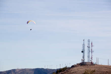 paraglider flying in front of a few antennas of mobile phone