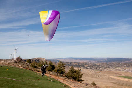 Paraglider taking off the earth in the mountains a sunny day