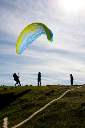 man trying to control the paraglide with friends Stock fotó