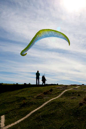 man learning to control the paraglide with friends