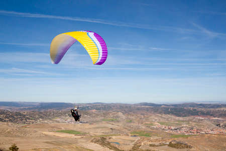 Paraglider feeling free flying in the mountains in a sunny day