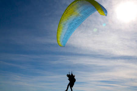 silhouette of a man with a paraglide in a sunny day with a sunny sky Stock fotó